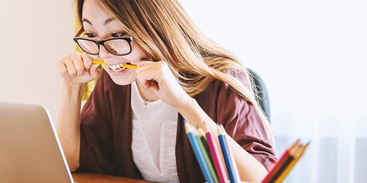woman at desk biting pencil