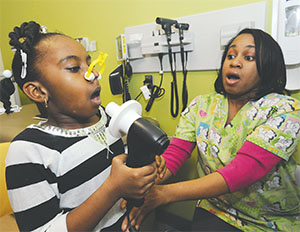 Faith Walker, 7, who has asthma, readies to take a breathing test as Monique Franklin, research assistant, coaches her on Jan. 23 at Johns Hopkins Children's Center in Baltimore, Md. Johns Hopkins research shows that poverty, more than race, drives asthma rates. (KIM HAIRSTON/BALTIMORE SUN/TNS)