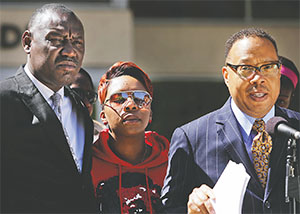 Michael Brown's mother, Lesley McSpadden, center, closes her eyes as attorneys Benjamin Crump, left, and Anthony Gray announce a wrongful-death lawsuit by Brown's relatives on April 23 at the St. Louis County Circuit Court in Clayton, Mo. (HUY MACH/ST. LOUIS POST-DISPATCH/TNS)