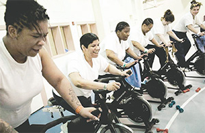 Women incarcerated at the Riverside Correctional Facility in Philadelphia take part in a spinning class run by Gearing Up. Amanda Cortes, second from left, lost 90 pounds in a year. (PHOTOS BY BASTIAAN SLABBERS FOR NPR/TNS)