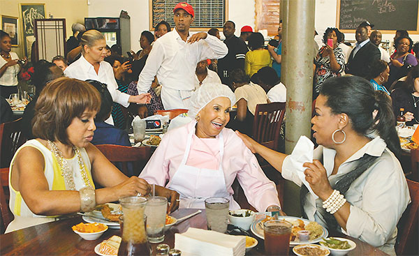 Sweetie Pie's owner Robbie Montgomery, center, greets Gayle King and Oprah Winfrey on Sunday afternoon, March 25, 2012, at her St. Louis restaurant where they ate a fried chicken dinner.(J.B. FORBES/ST. LOUIS POST-DISPATCH/TNS)