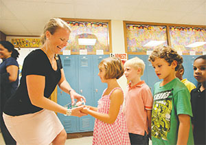 Kindergarten teacher Courtney Dohman dishes out a squirt of hand sanitizer to students at Holmes elementary School in Oak Park, Illinois, in September 2009. Schools across the U.S. used sanitizers to help fight the swine flu. (CHUCK BERMAN/CHICAGO TRIBUNE/TNS)