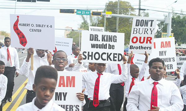 Miami students had some serious statements to share through their signage during the Dr. Martin Luther King Jr. parade on Monday in Liberty City.(KIM GIBSON/FLORIDA COURIER)
