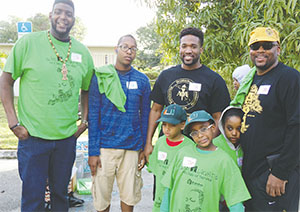 Alpha Phi Alpha Fraternity members Mario Lewis, Vernon Smith, Bryan Jones and youth participants pose for a picture outside the residence the chapter painted.