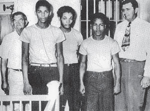 "Jailer Reuben Hatcher (far left) and Lake County Sheriff Willis McCall (far right), pose at the Lake County Jail with three of the ""Groveland Four,"" from left to right: Walter Irvin, Charles Greenlee and Samuel Shepherd.(COURTESY OF CHANGE.ORG)"