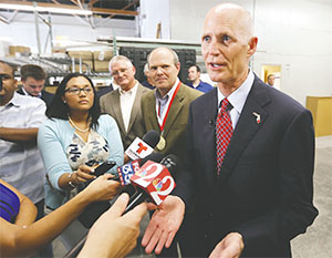 Florida Gov. Rick Scott talks to reporters during a visit to Bright Future Electric, an electrical contracting business with offices in Florida and Alabama, on June 11, 2015, in Ocoee.(JOE BURBANK/ORLANDO SENTINEL/TNS)