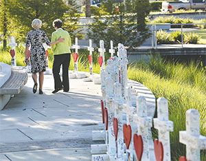 On the one-month anniversary of the Pulse nightclub massacre, Orlando City Commissioner Patty Sheehan, right, and a friend take a last look at crosses honoring the 49 victims.(JOE BURBANK/ORLANDO SENTINEL/TNS)