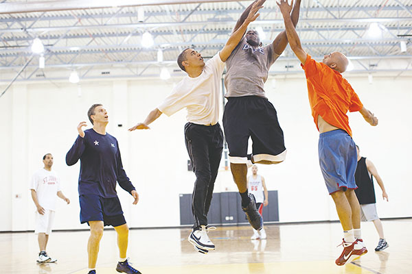 "President Barack Obama attempts to block a shot by personal aide Reggie Love during a basketball game on June 16 at Fort McNair in Washington, D.C. Secretary of Education Arne Duncan, left, watches the play. The president's checkup early this year showed that he's ""very healthy.''(UPPA/ZUMA PRESS/TNS)"