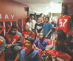 Tampa students hang out with Bucs in the team's RV parked at the Moffitt Cancer Center.