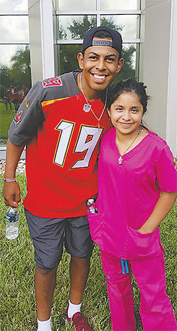 Roberto Aguayo, kicker for the Bucs, poses with a student.