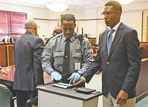 Dante Martin, right, a former member of Florida A&M University's Marching 100 band, looks at his family as he is fingerprinted on Oct. 31, 2014 after being found guilty of manslaughter in the fatal hazing of drum major Robert Champion.(RED HUBER/ORLANDO SENTINEL/TNS)