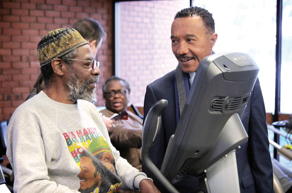 Kweisi Mfume chats with Charles Lowder in Baltimore on Jan. 9 during a campaign stop.