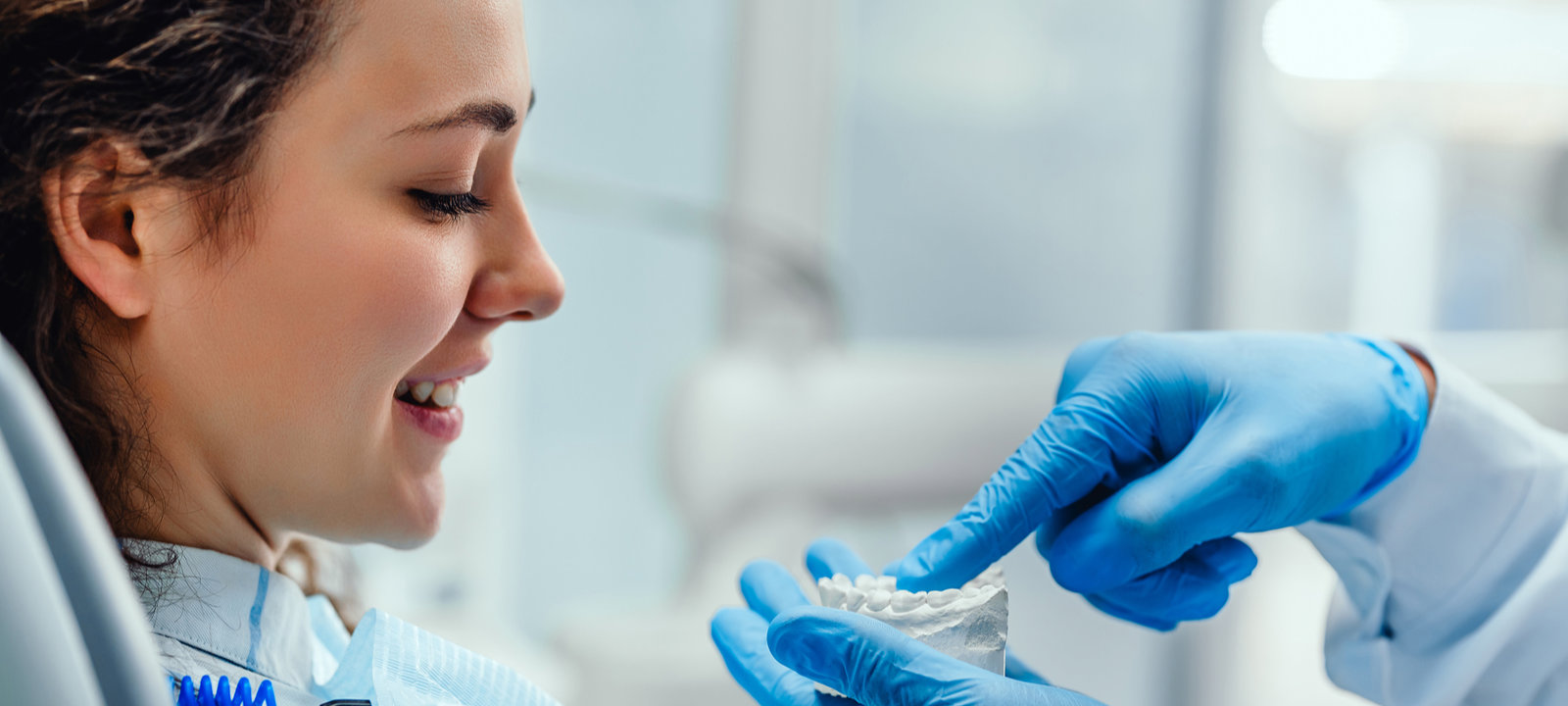 Male-Dentist-Explaining-His-Female-Patient-About-Teeth-Care