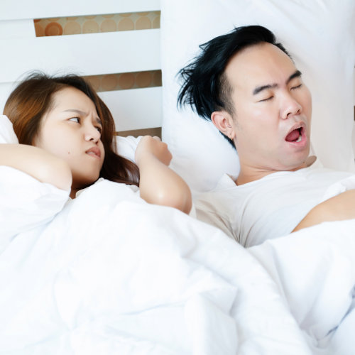 Couple-On-Bed-With-White-Mattress-Man-Snoring