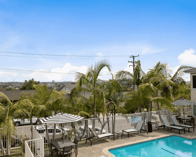 Pool at The Heights with view of treetops and umbrella