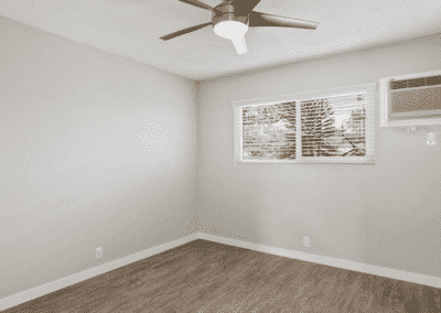 Bedroom with ceiling fan showing the window and AC unit