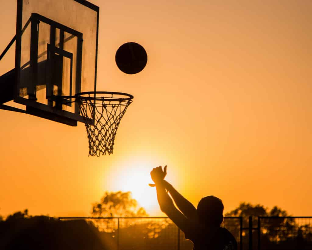 Person shooting a basketball with sunset in the background