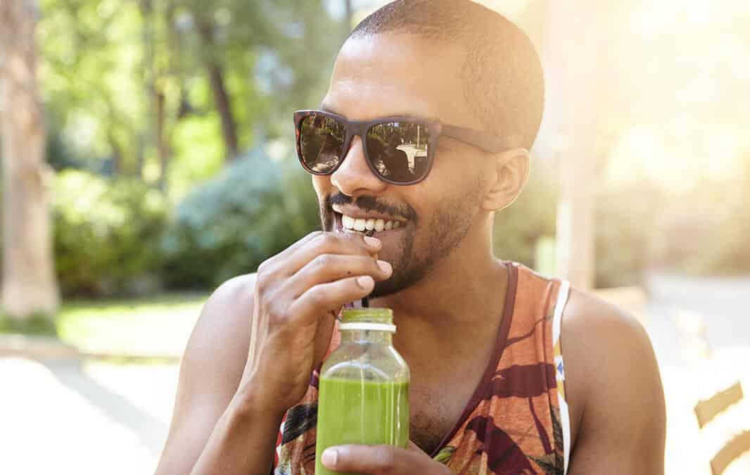 Man drinking smoothie under the sun
