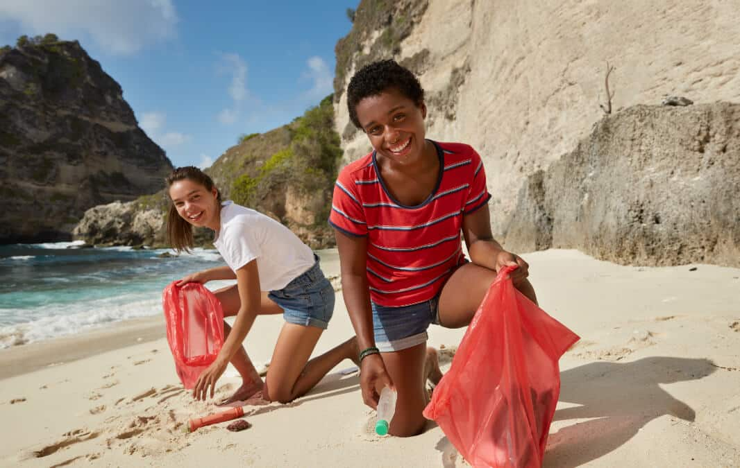Two girls picking up trash on the beach sand