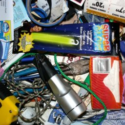 Contents in a junk drawer including a tape measurer, string, tape, coupons