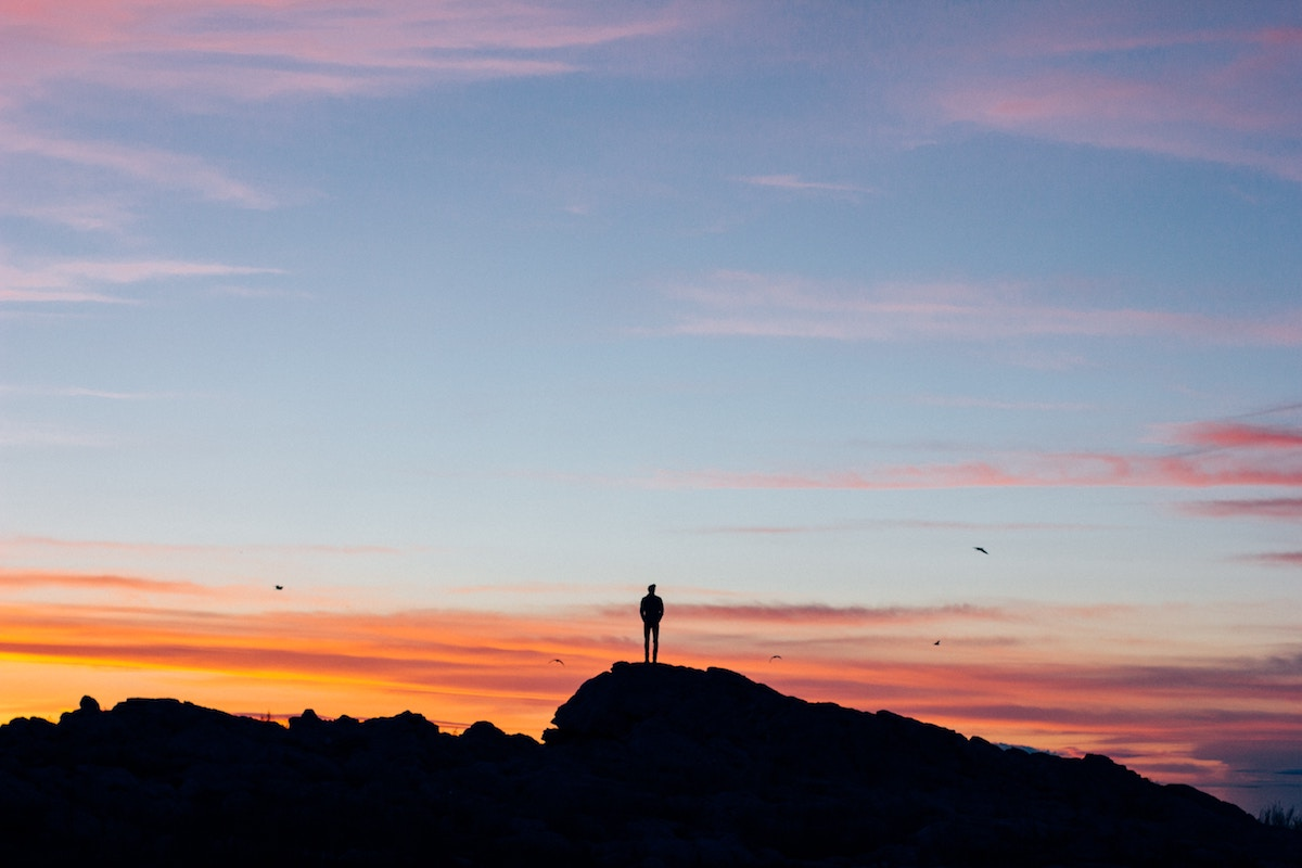 Man alone on mountain at sunset