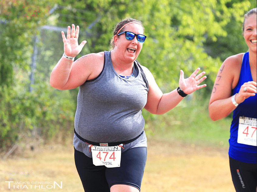 Woman has fun on the run course at Jack's Generic Tri, Smiling and waving with friend doing a triathlon, Official Photo from FinisherPix