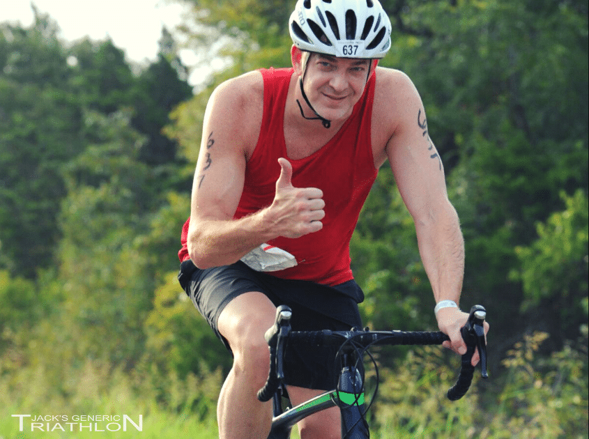 Man in red tank rides the bike at Jacks Generic Tri in Austin Texas, Official Photo from FinisherPix
