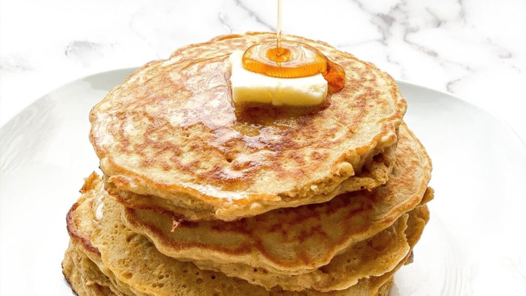 Stack of banana oatmeal pancakes with syrup being drizzled on top