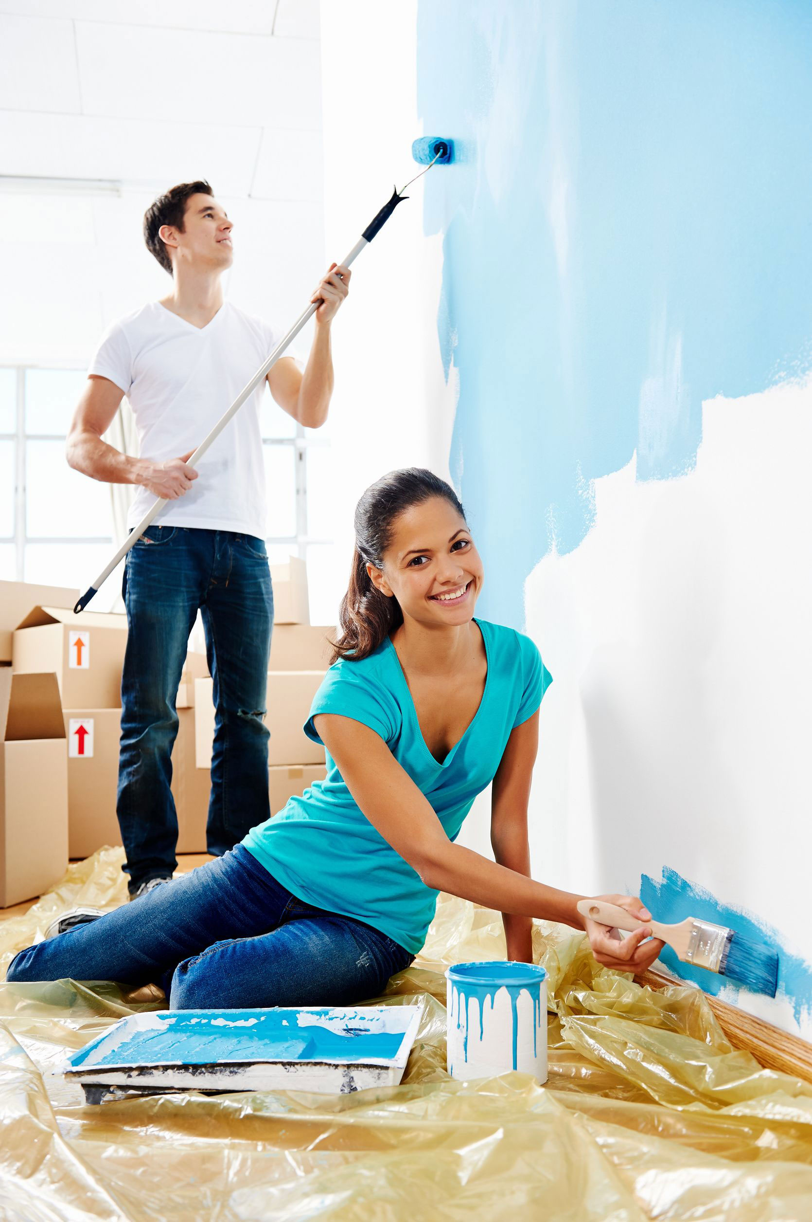 photo of a young couple painting their new home