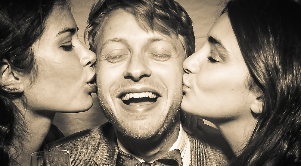 man with two women kissing him