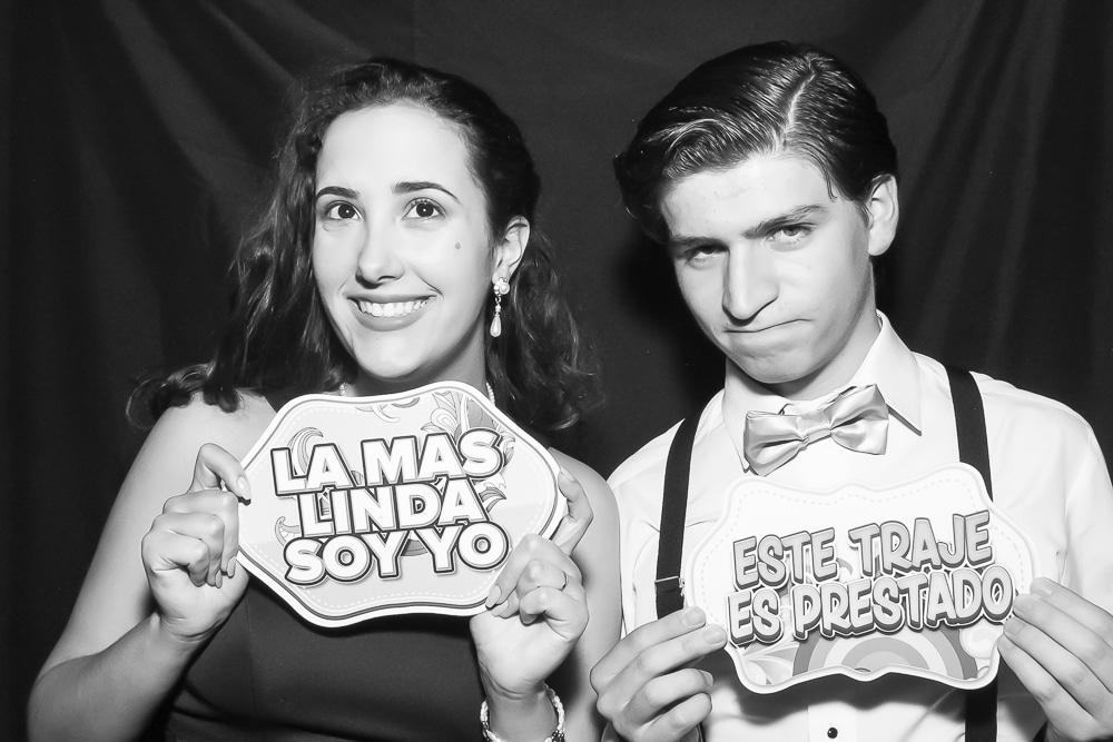 Young couple with signs in photo booth