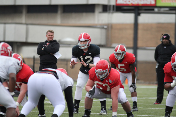 Quarterback Kurt Hess (12) prepares to take the snap as head coach Eric Wolford (back left) looks on during Saturday's scrimmage. The Penguins open their season Thursday at 7:30 p.m. at Stambaugh Stadium against the University of Dayton. Photo by Dustin Livesay/The Jambar.
