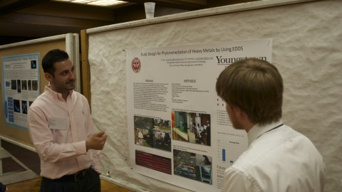 Yener Ulus, a third semester biology graduate student, showcases his research on phytore-mediation of heavy metals. Photo by Frank George/ The Jambar.