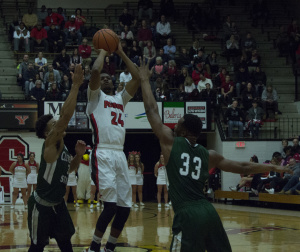 Youngstown State University guard Cameron Morse (24) pulls up for a jumper over two Cleveland State University defenders.