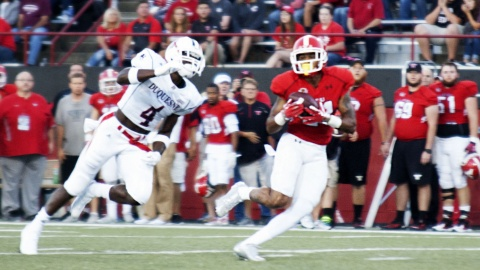 Youngstown State University wide receiver Darien Townsend (21) makes and over the shoulder catch in front of Duquesne University defensive back Daquan Worley (4).