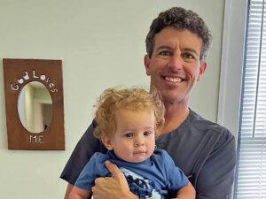 Third generation chiropractor holding fourth generation patient.
