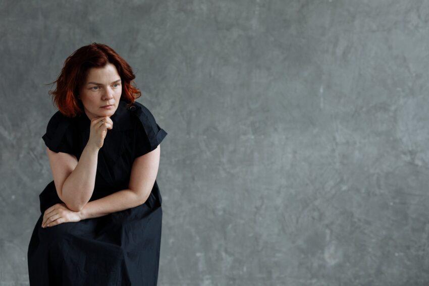 woman in black dress thinking