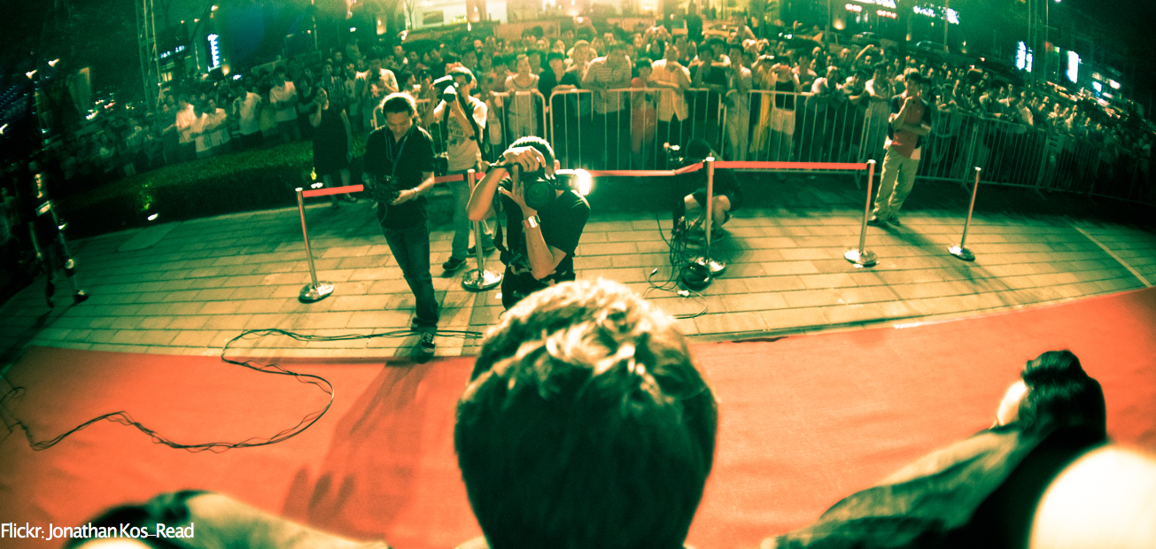 A first person picture of a man being photographed on a red carpet by photographers and crowds of people