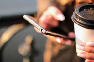 A figure holding a smartphone in one hand a cup of coffee in the other