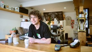 A smiling barista, standing with a cup of coffee in a nice café