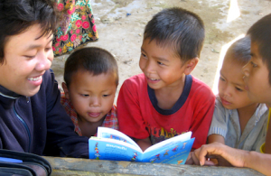A boy in a rural village in Laos reading aloud to his smiling family