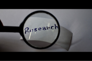 A black and white image of a magnifying glass magnifying the word 'Research'
