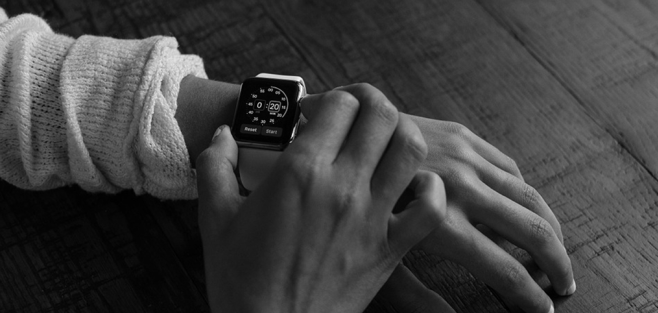 A black and white image of a man checking his watch