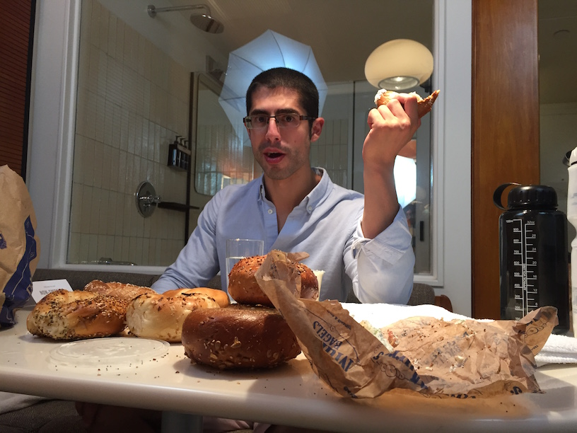 Michael Sorace sitting at the table, bagels in front of him, trying to make it through another