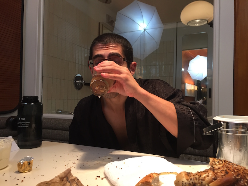 Michael Sorace drinking water that an onion bagel was soaked in. The water is yellow and gross.