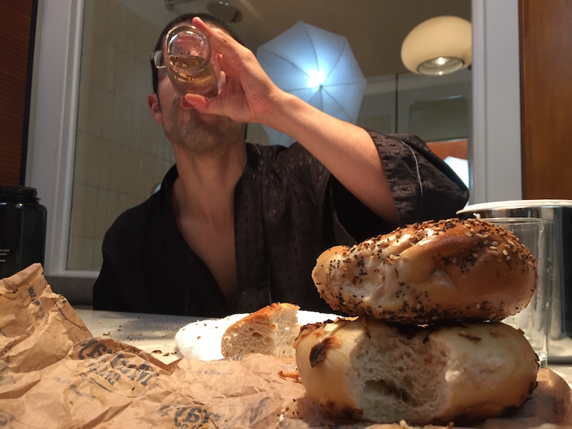 Michael Sorace finishing water that an onion bagel was soaked in. The water is yellow and gross.