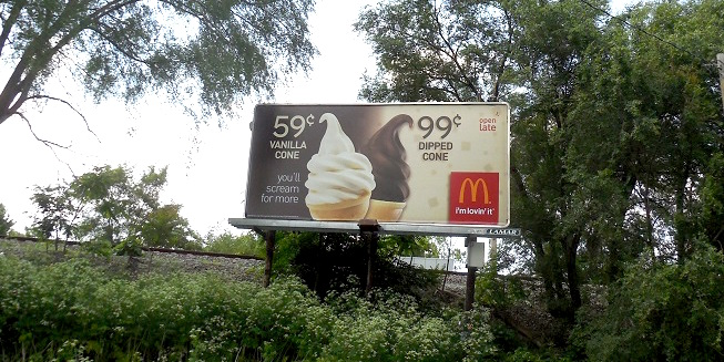A McDonald's billboard on the side of a highway.