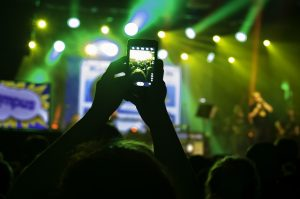 A person at a concert taking a picture with her mobile phone