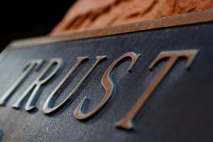 "A copper plaque with the word ""Trust"" on it."