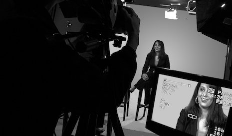 A woman sitting on a stool in front of a camera in a production studio